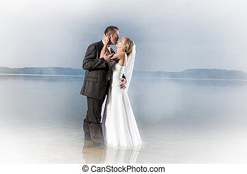 Young couple in a misty lake in a passionate kiss