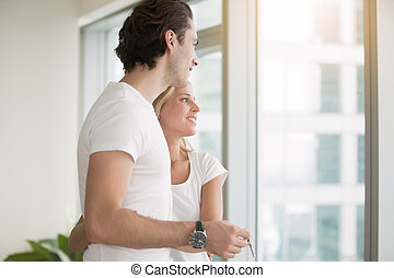 Young couple, in a modern flat, holding key