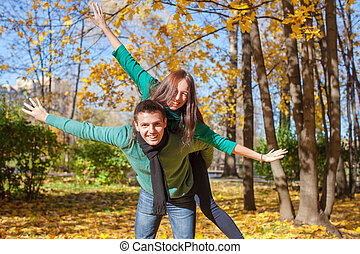 Young couple in autumn park on a sunny fall day