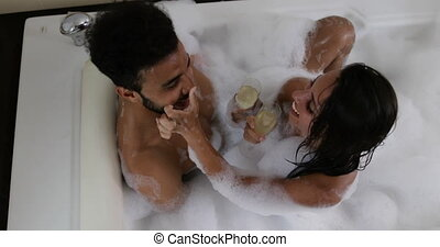 Young Couple In Bath Together Drink Champagne Talking Top...