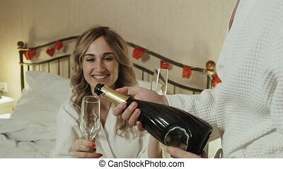 Young couple in bathrobes celebrates anniversary. The guy ...