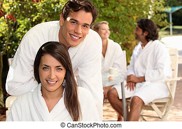 Young couple in bathrobes sitting on a terrace with friends