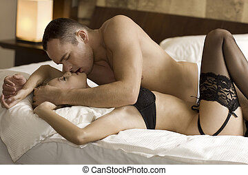 young couple in bed - intimate young couple during foreplay...