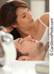 Young couple in bed next to an alarm clock
