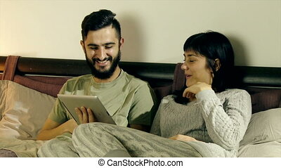 Young couple in bed smiling reading