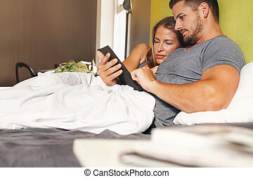 Young couple in bed using a digital tablet