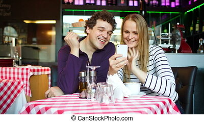 Young couple in cafe having a video chat on smartphone