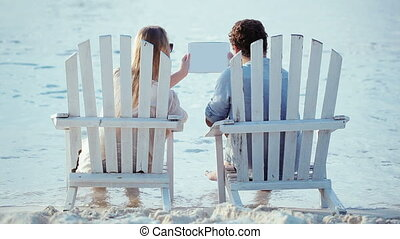 Young couple in chaise-longues holding pad and looking at it