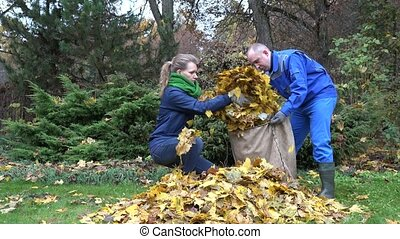 young couple in colorful clothes put raked leaves in big...
