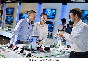 Young couple in consumer electronics store looking at latest...