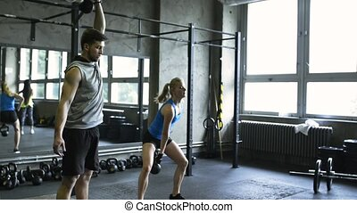 Young couple in crossfit gym lifting kettlebells
