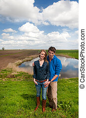 Young couple standing in typical Dutch landscape