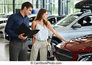Young couple in elegant summer time clothes choose a new car at car dealership