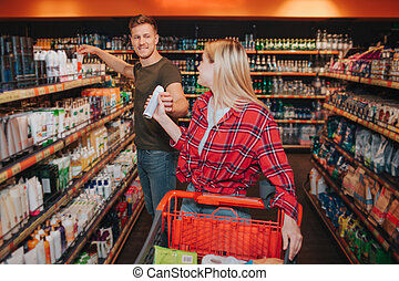 Young couple in grocery store. Woman get deodorant from man. He stant at hygiene shelfs. People look at each pther and smile. Cheerful buyers.
