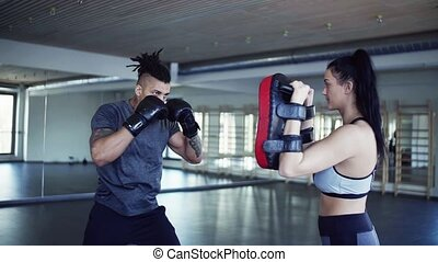 Young couple in gym with boxing gloves doing exercise indoors.