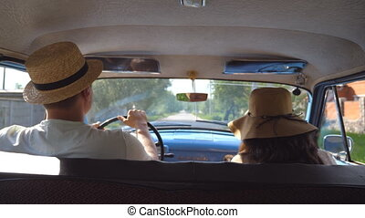 Young couple in hats driving on country road in classic vintage car. Unrecognizable pair riding into old auto. Man and woman sitting at the front seat of a retro automobile. Trip concept. Slow motion
