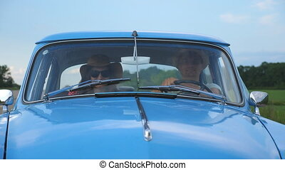 Young couple in hats riding at vintage car during summer travel. Happy man and woman sitting at the front seat of old retro car and enjoying ride and holidays. Road trip concept. Slow motion Close up