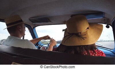Young couple in hats riding at vintage car during summer...