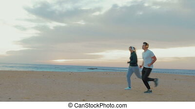 Young couple in headphones running on the beach