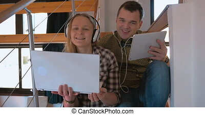 Young couple in heaphones at home enjoying music