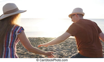 Attractive man and woman enjoying romantic evening on the beach