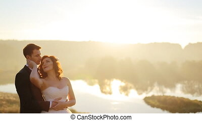 Young couple in love bride and groom on the background of sunset, straightens hair backlight, field of wheat, soft and romantic, white dress, tie, nature, shot in slow motion  close up