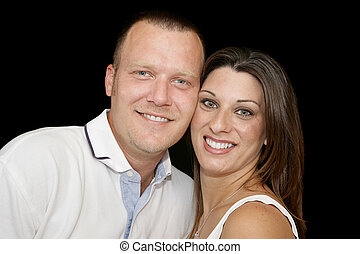 Closeup portrait of a young married couple over black background.