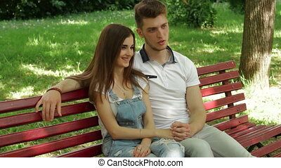young couple in love cute talking on a bench in the Park