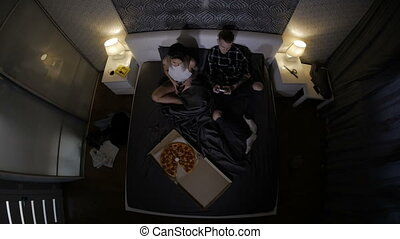 young couple in love eating pizza and playing video games. top view