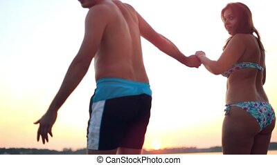Young couple in love having fun jump off the yacht into the sea dive at sunset. Happiness and vacation concept.