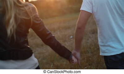 Young couple in love holding hands walking in field at...