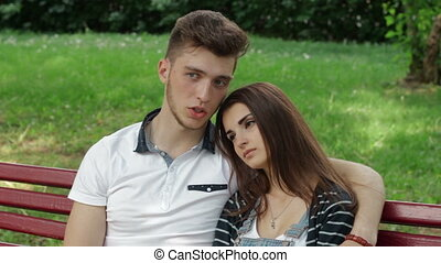 young couple in love hugs and talking on a bench