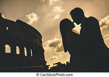 Young couple in love in front of the Colosseum in Rome at sunset