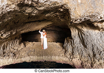 young couple in love inside a cave - portrait of a young...