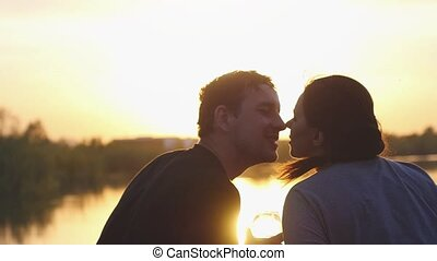 Young couple in love kissing and drinking wine by the sea at...