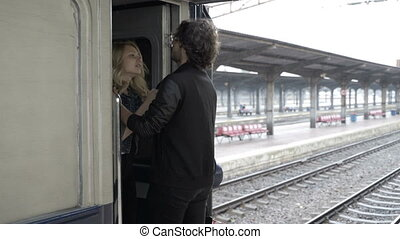 Young couple in love kissing and hugging goodbye in railway station before departing on rainy day