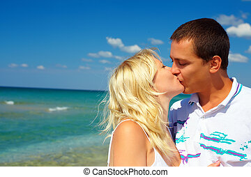 young couple in love kissing on beach