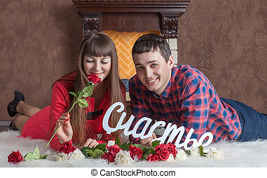 Young couple in love lies near the fireplace on carpet