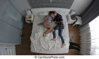 Young couple in love lying in bed. top view