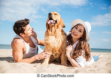 Young couple in love lying on the beach with dog