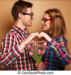Young couple in love make a heart and hands are holding a...