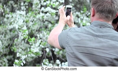 Young couple in love makes selfie in a public park: smart phone.  A flowering tree background
