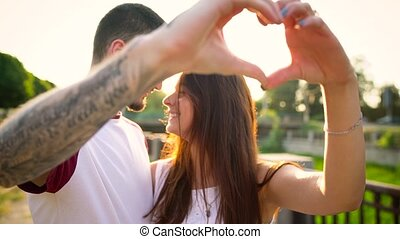 Young couple in love making heart symbol with their hands at...