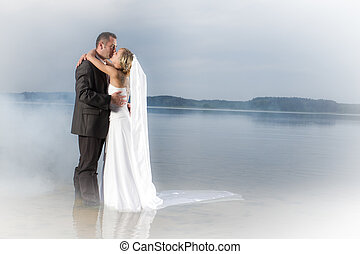 Young couple In love on a lake in the fog