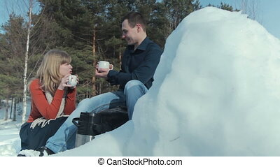 Young couple in love on a winter vacation enjoying the nature and drinking hot tea