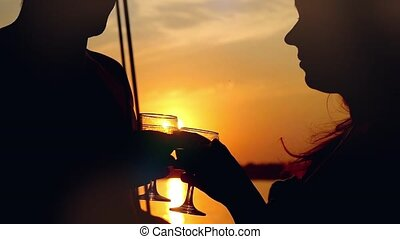 Young couple in love on sail boat with glasses of wine at sunset in slowmotion on the sun background