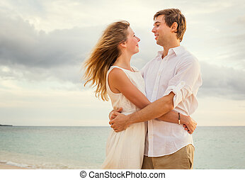 Young couple in love on the beach sunset