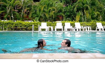 Young couple in love relaxing in the swimming pool have fun...