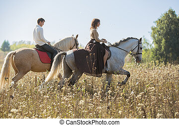 Young couple in love riding a horse