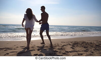 Young couple in love running on sea beach, man hug his woman and spinning around. Girl jumps into her boyfriend hands and he whirling her at beautiful seaside. Pair having fun at vacation. Slow motion